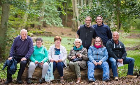 A group of middle-aged people sat in a forest